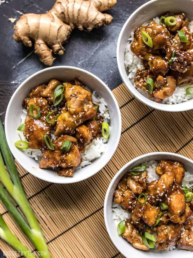 A picture of saucy, sesame chicken over rice.