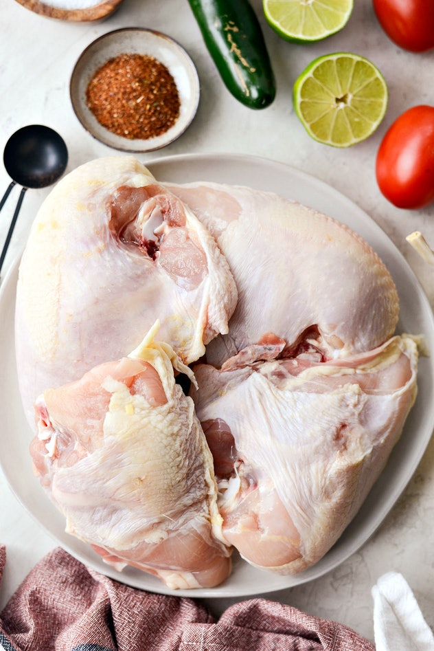 An image of raw chicken surrounded by herbs and spices.