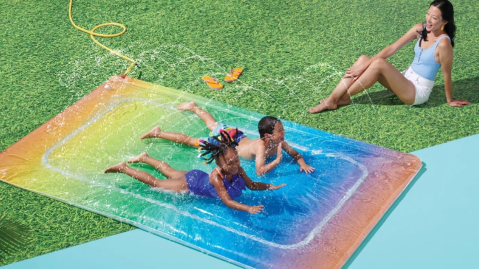 A picture of children sliding on a rainbow inflatable water slide.