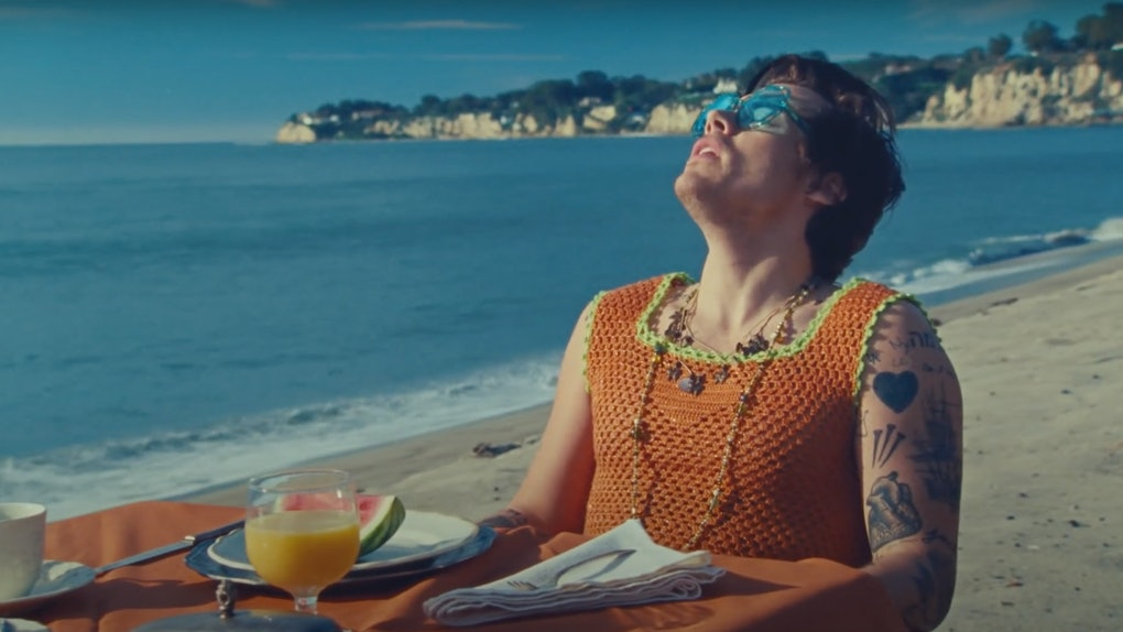 "Harry Styles sits at a dining table on the beach in the music video for ""Watermelon Sugar."""