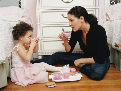 A mom has a tea party with her daughter on the floor