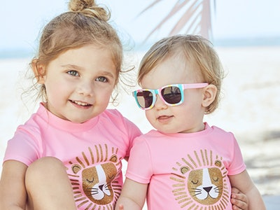 Two blonde girls in matching pink beach outfits from carter's