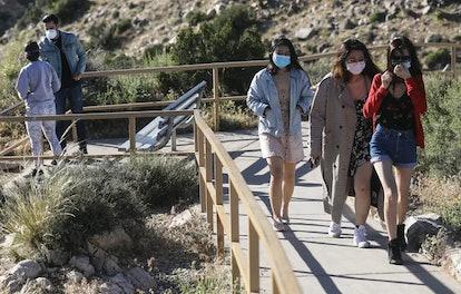 Visitors wear face masks at Joshua Tree National Park in California on May 18, 2020. Wearing masks a...