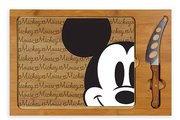 A cheeseboard has Mickey Mouse on the front and a cheese knife on the side.