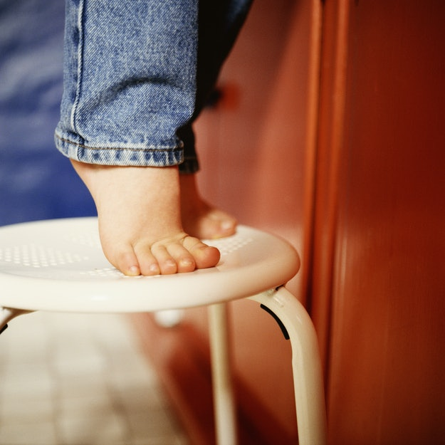 child tip toes on a stool