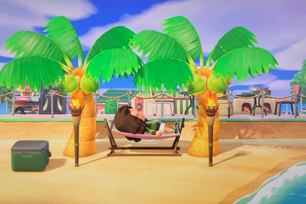A young woman lays on a hammock on her beach in 'Animal Crossing: New Horizons.'