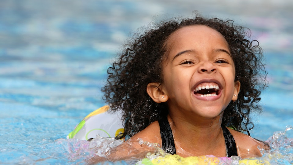 Little girl with a big happy smile swimming in a pool