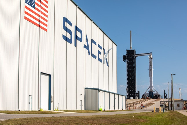 A SpaceX Falcon 9 rocket, with the Crew Dragon atop, at the launch pad.