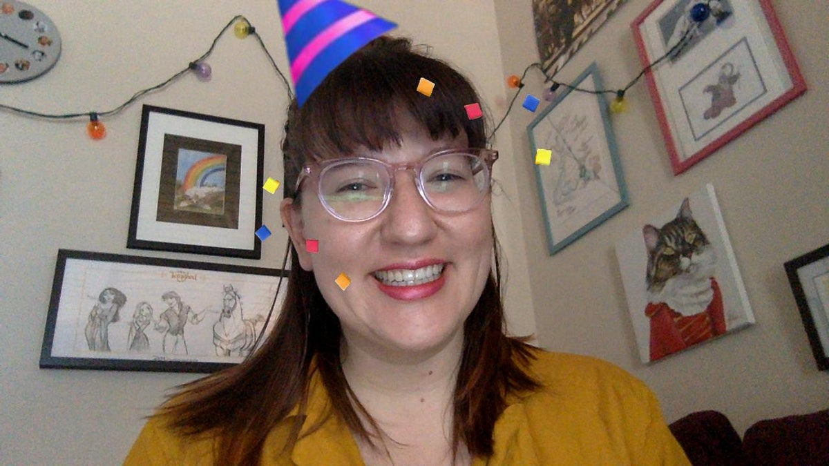 A happy woman smiles with a party hat filter on her head.