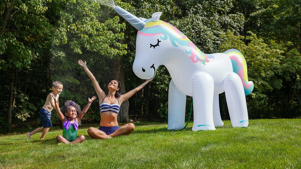 A young family sits in their backyard and plays under a giant unicorn sprinkler.