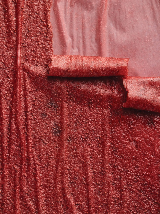 Bright red strips of fruit leather rolling down at different lengths.
