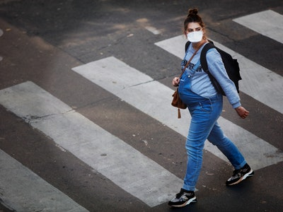 a pregnant woman in a face mask walks in Paris during COVID-19