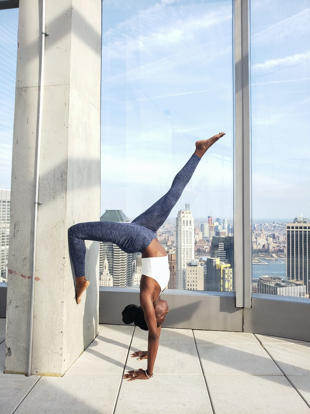 A woman in yoga apparel does a handstand on a rooftop on a sunny day.