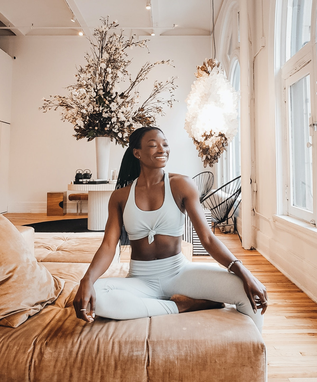 A woman in white yoga apparel smiles and sits on a brown couch in a bright room.