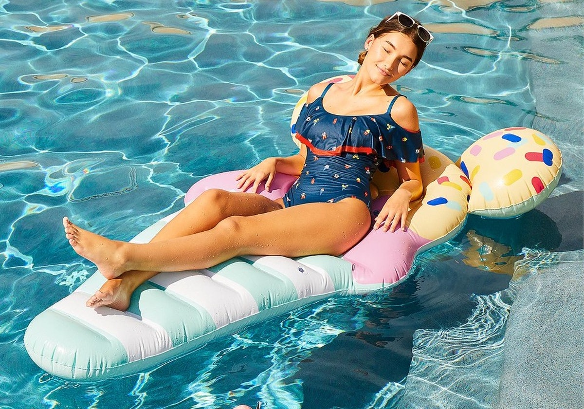 A woman lounges on a Mickey Mouse ice cream pool float in the summer.