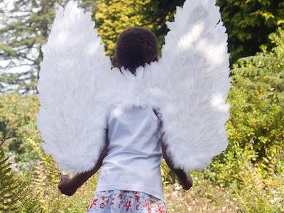 Child walks through woods in wings