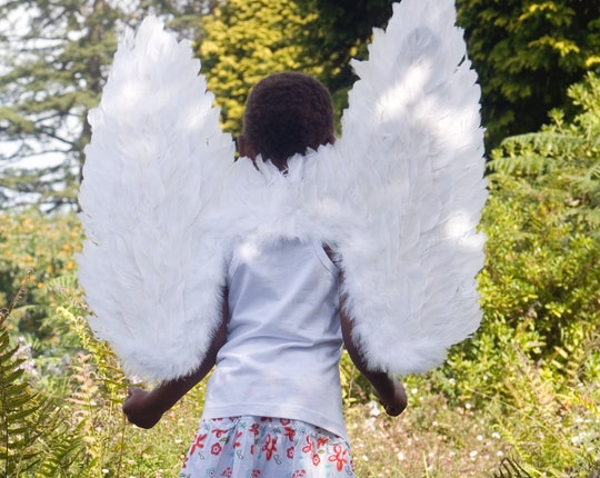 Child walks through woods in wings