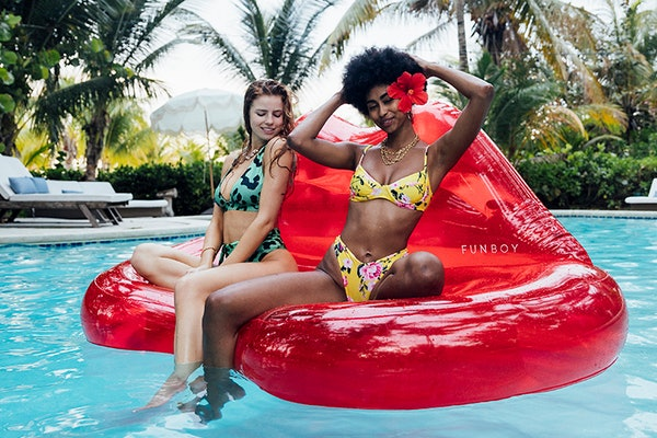 Two friends sit on a clear red lips inflatable couch while chilling in the pool on a summer day.
