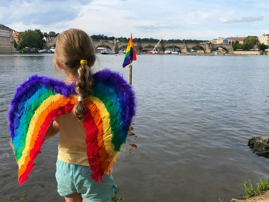 A girl in rainbow wings holds a flag