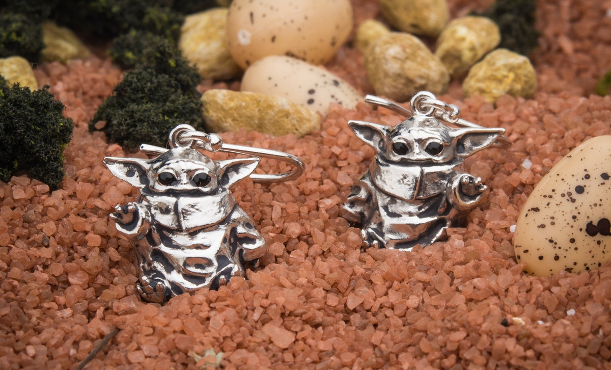 A pair of sterling silver baby Yoda earrings from 'Star Wars' sits on top of brown gravel.