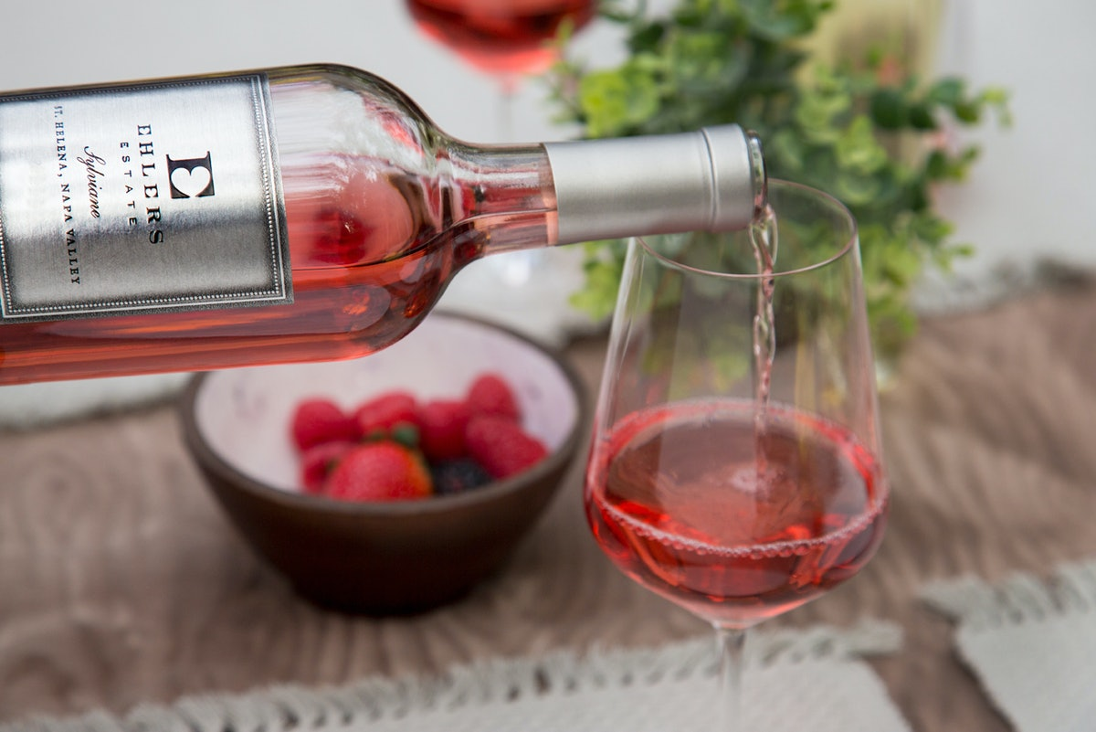 A bottle of Ehlers Estate rosé is being poured into a glass.