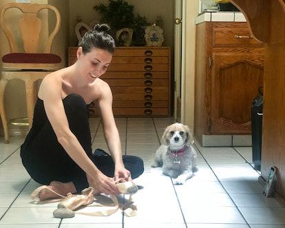 Ballerina Tiler Peck sitting on the floor, putting on her pointe shoes. Her little white dog, Cali, ...