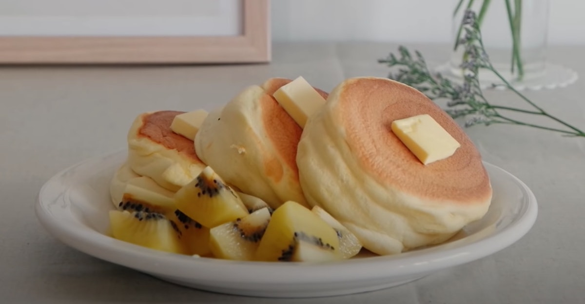 Three Japanese soufflé pancakes are on a plate with butter on top and fruit on the side.