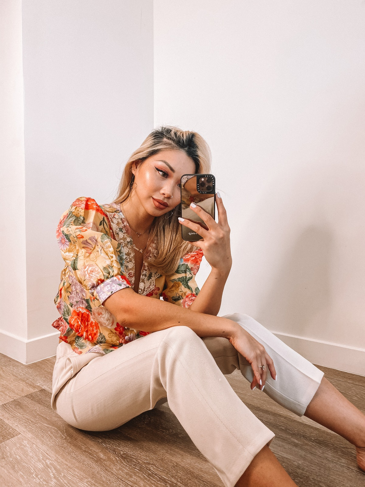 A woman with a floral top and tan capris sits on the floor and takes a mirror selfie.