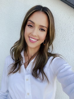 Jessica Alba beaming in a white shirt, in the sunshine outside her home.