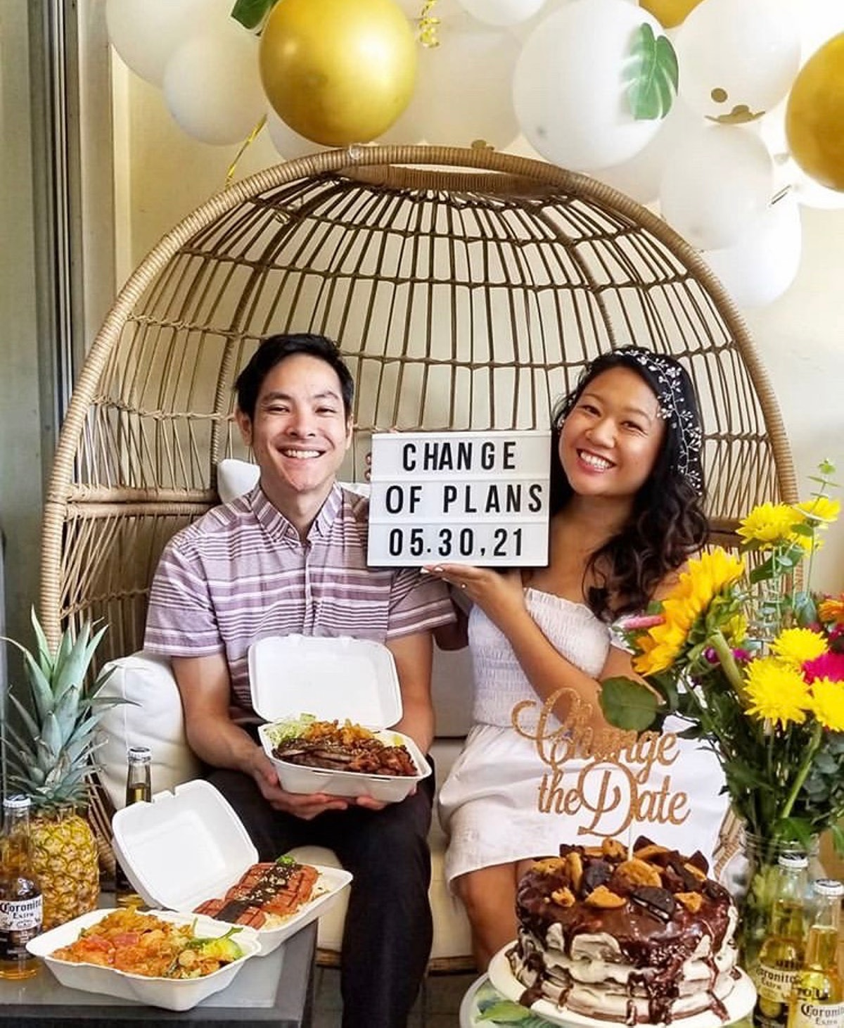 A happy couple announces their new wedding date with a cake, food, and drinks over Zoom.
