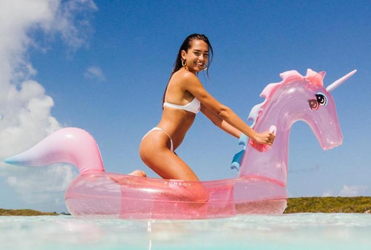A woman sits on a pink unicorn pool float in the water.