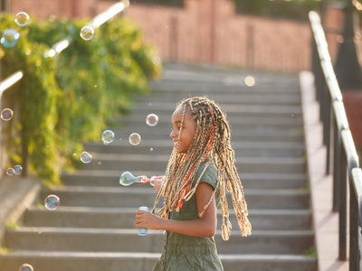 Joyful girl with braids catching soap bubbles.