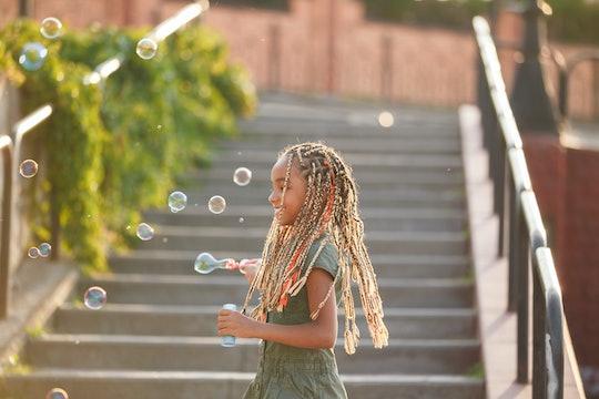 Joyful girl with braids catching soap bubbles.
