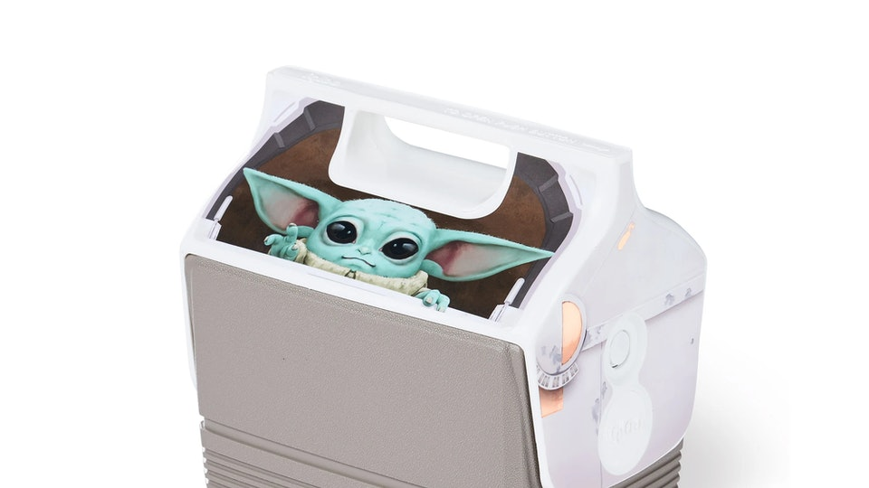 A classic Igloo cooler with handle top. On the front facing top slanted side, an image of The Child or Baby Yoda from The Mandalorian.