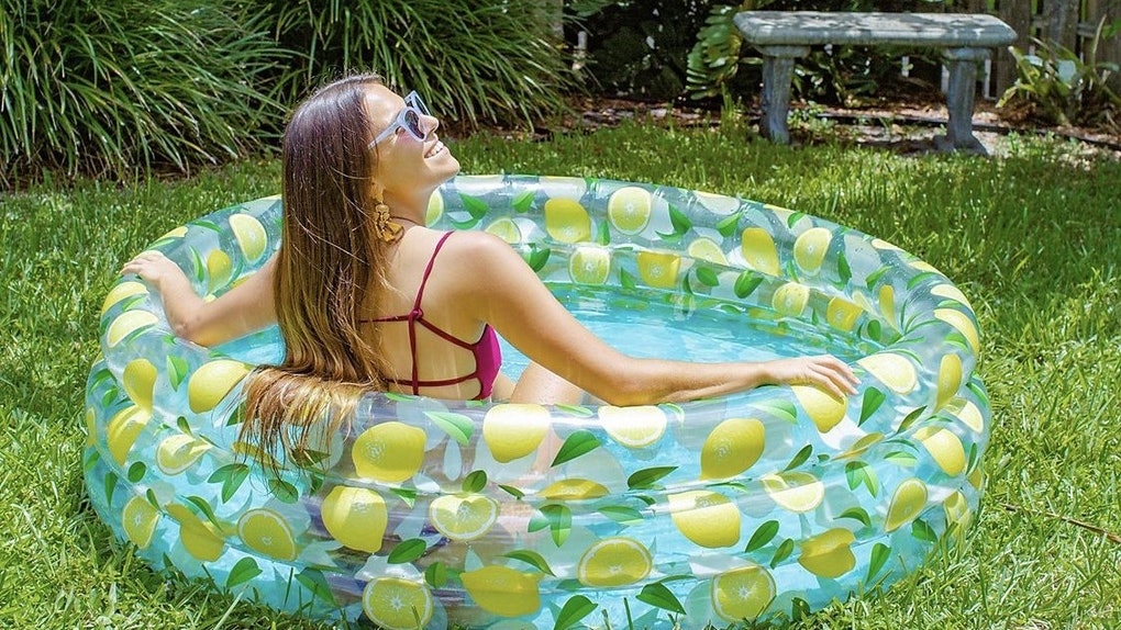 A woman sits in an inflatable pool in her backyard during the summer.