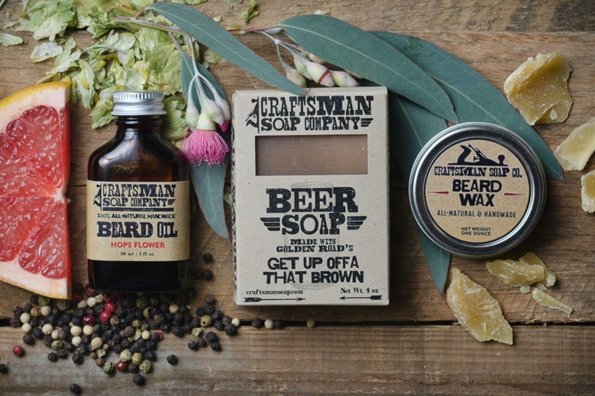 Beard oil, soap, and beard wax are placed on a table next to a slice of grapefruit and flowers in a rustic display.