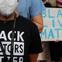 """A woman wears a shirt reading """"Black doctors matter"""" at a protest. Talking About Racism Must Be A Part Of Health Care, According To A Doctor"""