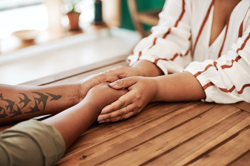 Two women hold hands on a wooden table. How To Handle Emotional Burnout As You Keep Pushing For Anti-Racist Change