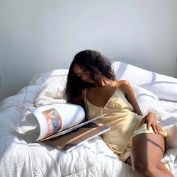 Model in a yellow slip dress flips through a book while in bed.
