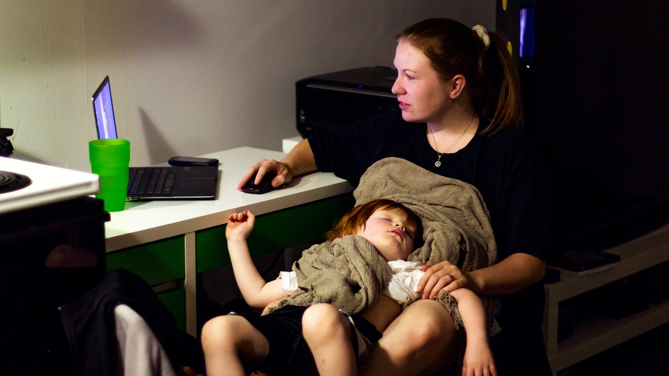 Mom on laptop with child on lap