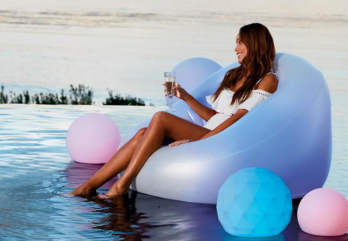 A woman sits on a glow pool float with a glass of wine in her hand.