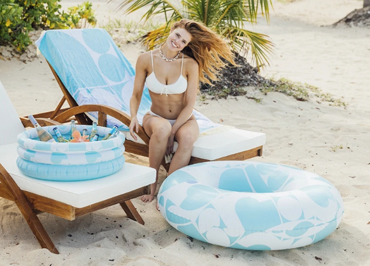 A woman in a white bikini smiles while sitting on a lounge chair next to an inflatable cooler and pool tube.