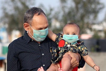 A grandfather and grandson in India wearing masks.