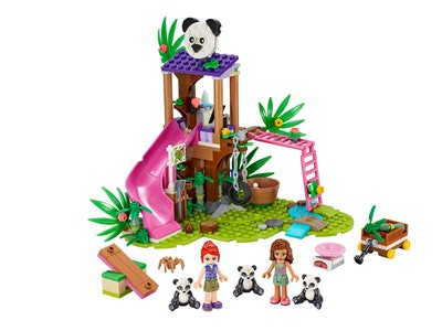 Two LEGO Friends kids beside three panda characters in front of a LEGO jungle gym.