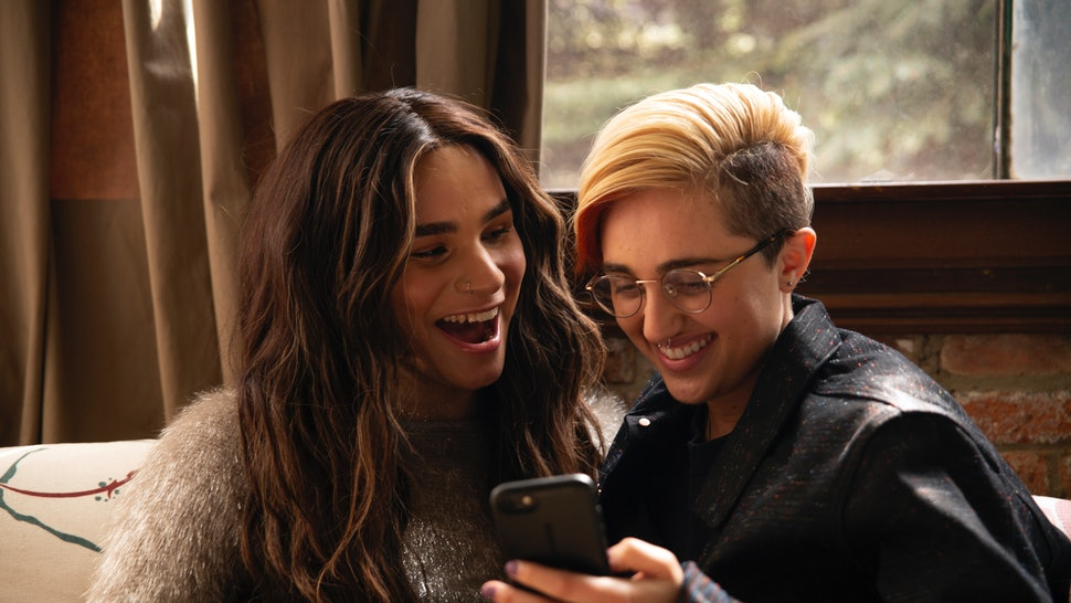 A transfeminine non-binary person and transmasculine gender-nonconforming person looking at a phone and laughing. Creating found family and queer joy is an important part of queer survival.