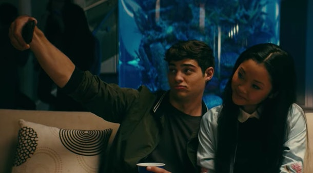 Lara Jean and Peter Kavinsky take a selfie, while sitting on a couch in 'To All The Boys I've Loved Before.'