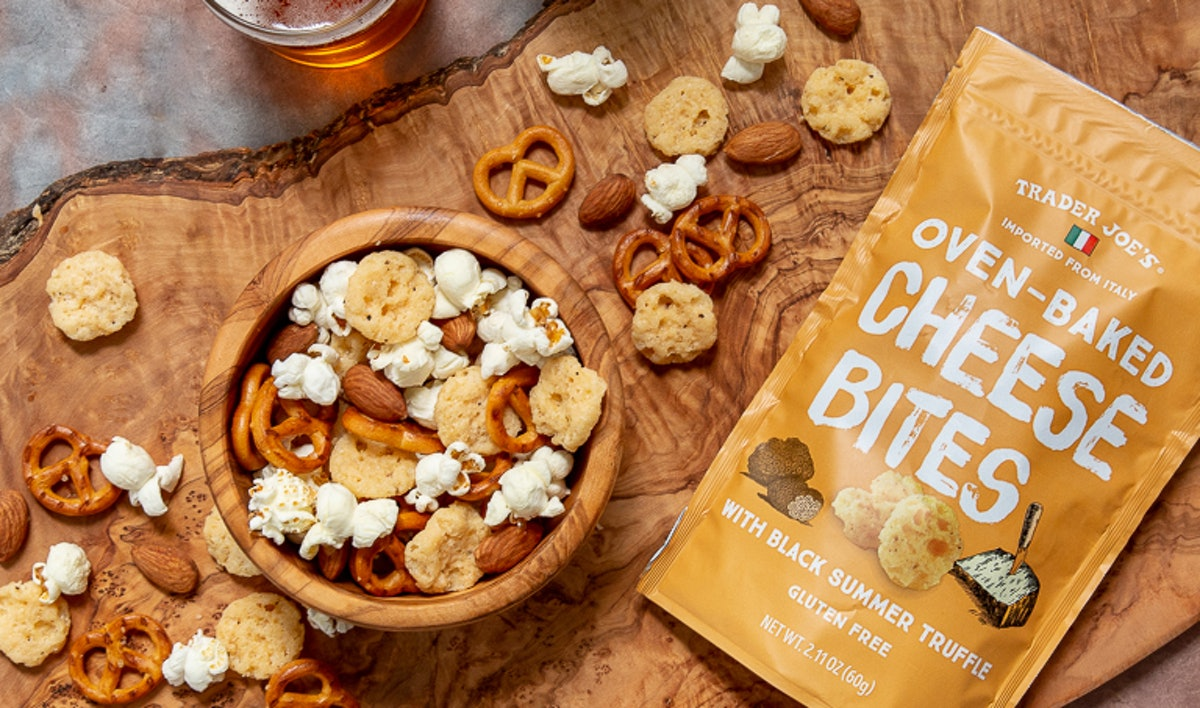 A bag of Trader Joe's oven-baked cheese bites sits next to a bowl of cheesy truffle snack mix.