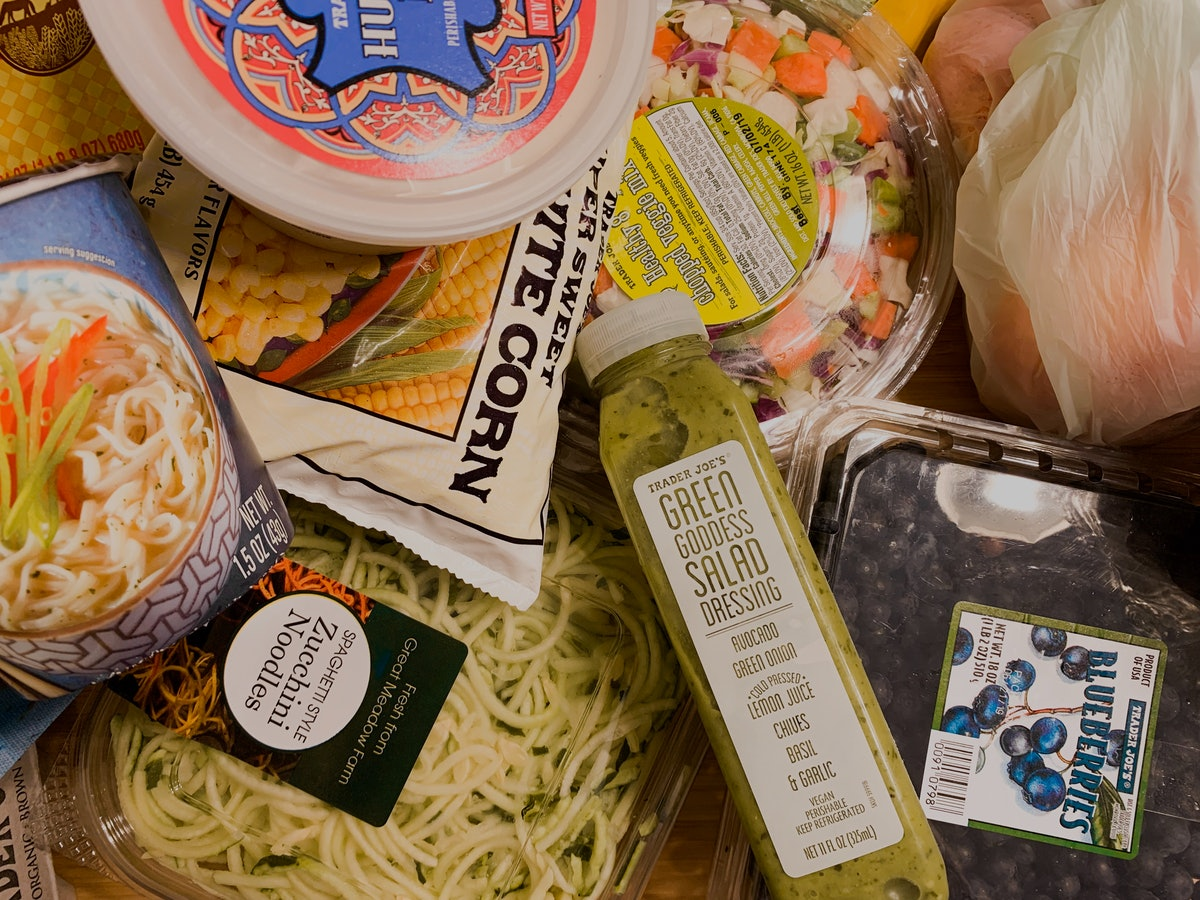 A kitchen table is filled with groceries and snacks from Trader Joe's.