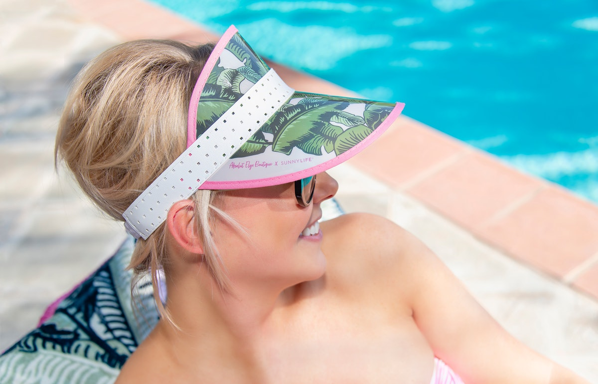 A happy woman wearing a sun visor with palm tree leaves on it sits by the pool on a summer day.