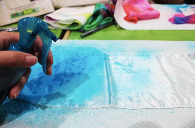 This tie-dye hack to do with your kids involves using a spray bottle to create a tie-dyed look on a scarf.